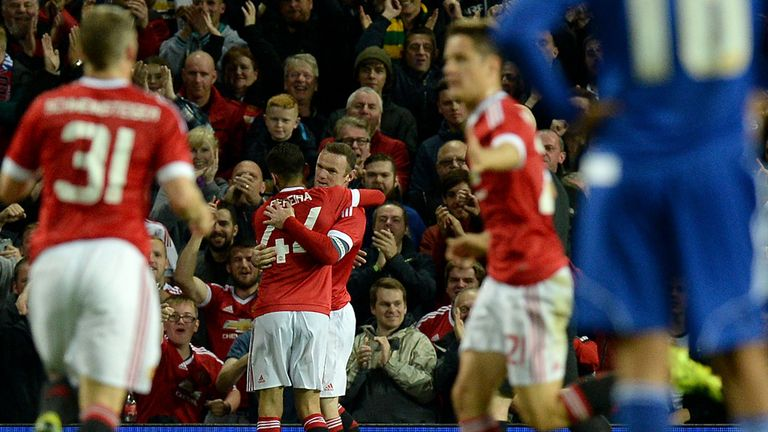 Rooney celebrates with team-mates after his goal