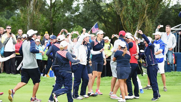 Players and officials of Team USA celebrate after winning the singles matches of the Solheim Cup