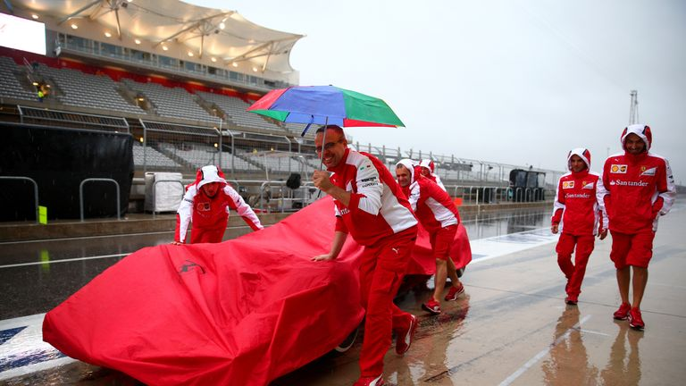 Ferrari mechanics keep their car covered from the elements as rain continues to batter Austin on Saturday