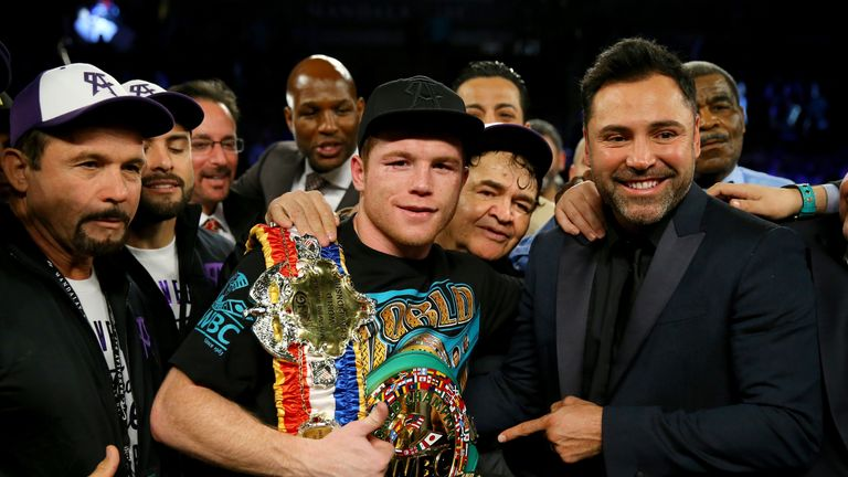 Canelo Alvarez celebrates with promoter Oscar De La Hoya after defeating Miguel Cotto by unanimous decision in Las Vegas