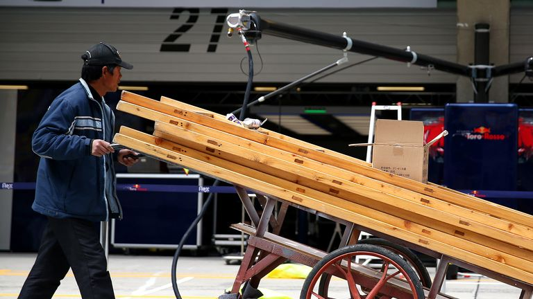 F1 in the slowlane: A workman pushes equipment through the pitlane ahead of the Chinese GP - Picture by Dan Istitene, Getty Images