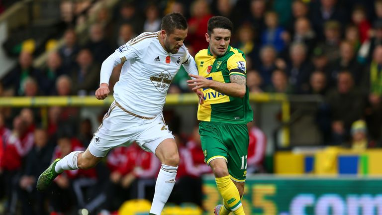 Gylfi Sigurdsson (L) of Swansea City and Robbie Brady of Norwich City compete for the ball