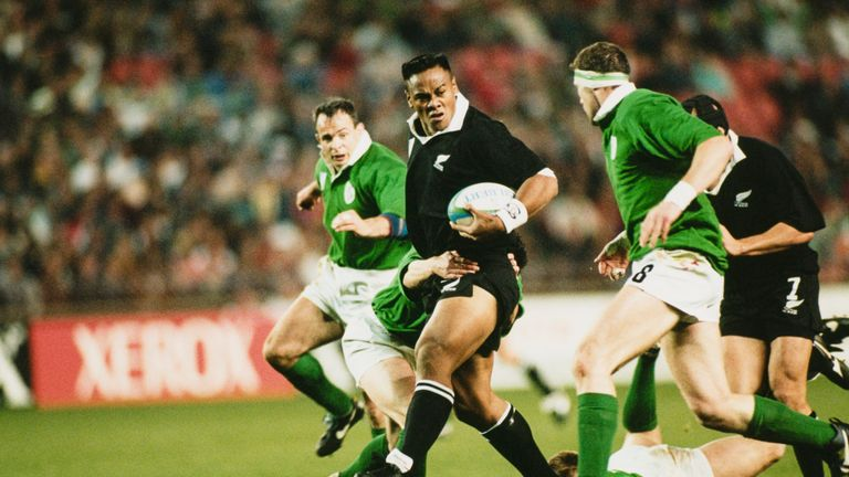Jonah Lomu looks for support as he is tackled by Ireland's Eric Elwood