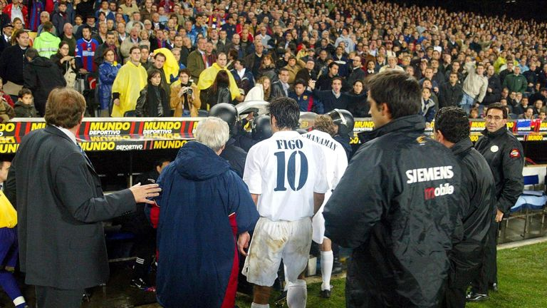 Figo leaves the pitch as play was suspended during the La Liga match between Barcelona and Real Madrid