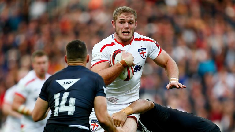 Tom Burgess of England is tackled by Lewis Brown and Ben Matulino of New Zealand
