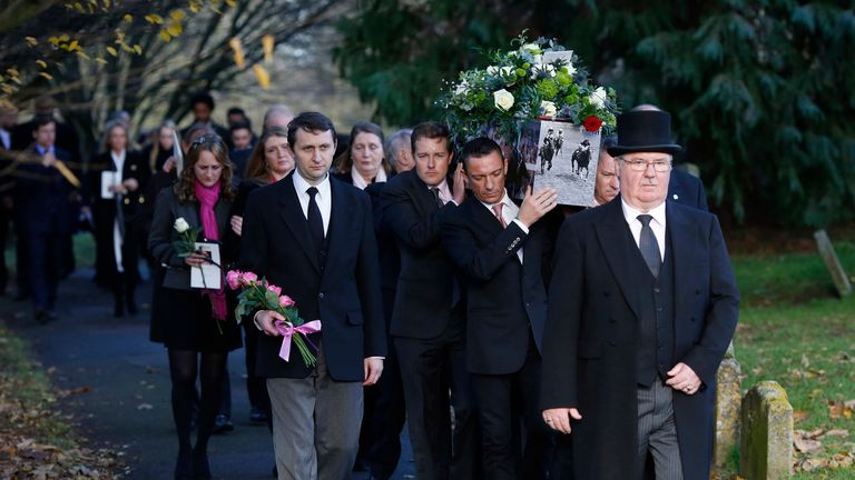 Frankie Dettori and other jockey's carry out the coffin after the funeral service for Pat Eddery