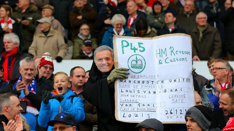 A Stoke City fan wears a Jose Mourinho mask as he poses with a P45 for Manchester United manager Louis van Gaal