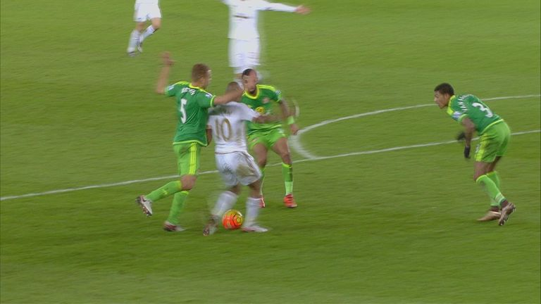 Andre Ayew falls with Wes Brown behind him but kicks the ground with his left foot