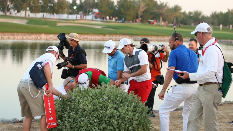 McIlroy helps Andy Sullivan hunt for his ball at the ninth, but DeChambeau did not join the search party