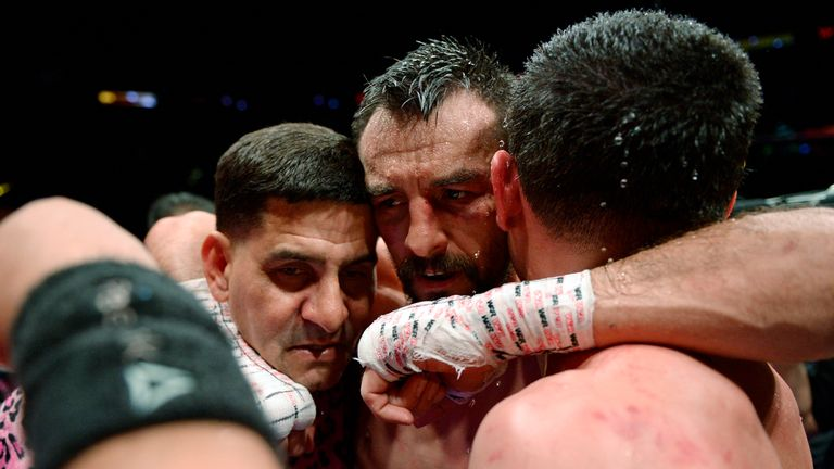 Guerrero (middle) hugs Garcia (R) and trainer Angel Garcia after the bout