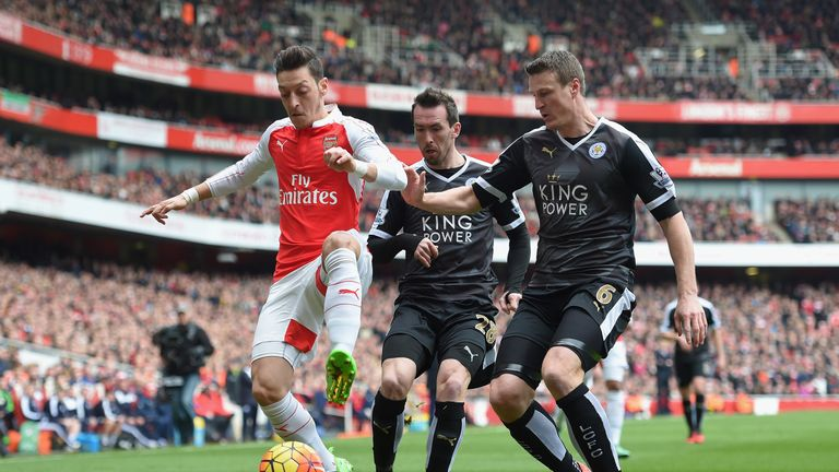 Mesut Ozil (left) holds off the attentions of Robert Huth