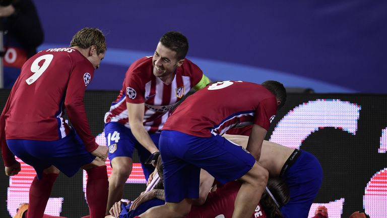 Atletico Madrid players mob Juanfran after his penalty secured victory against PSV