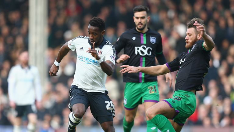 Moussa Dembele of Fulham (L) is tackled by Nathan Baker of Bristol City