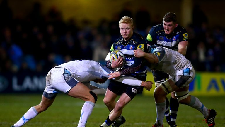 Tom Homer of Bath is tackled by Calum Green and Chris Harris of Newcastle