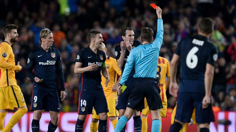 Referee Felix Brych [centre] shows the red card to Atletico Madrid's Fernando Torres [second left]