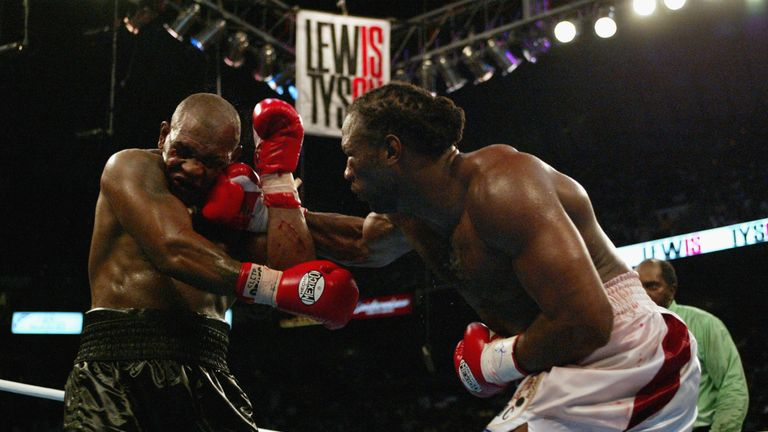 Lennox Lewis hits Mike Tyson with a right hook during their WBC and IBF title fight in 2002