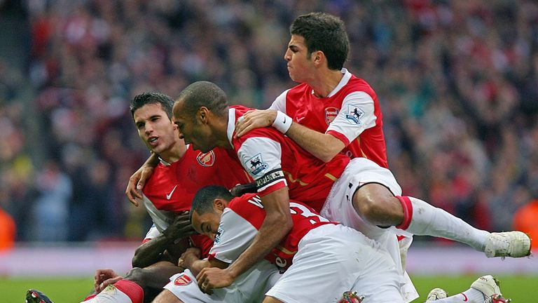Walcott celebrating with Robin van Persie, Thierry Henry and Cesc Fabregas