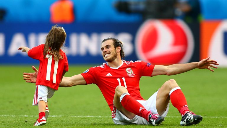 Gareth Bale celebrates victory on the pitch with his daughter