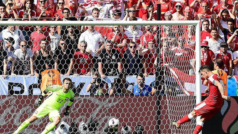 Switzerland's midfielder Granit Xhaka (R) misses his penalty attempt