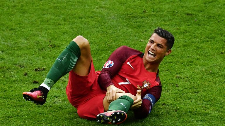 Cristiano Ronaldo clutches his left leg after a heavy collision with Dimitri Payet