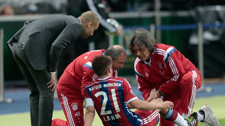 Hans-Wilhelm Muller-Wohlfahrt (right) treats Philipp Lahm as Guardiola watches on