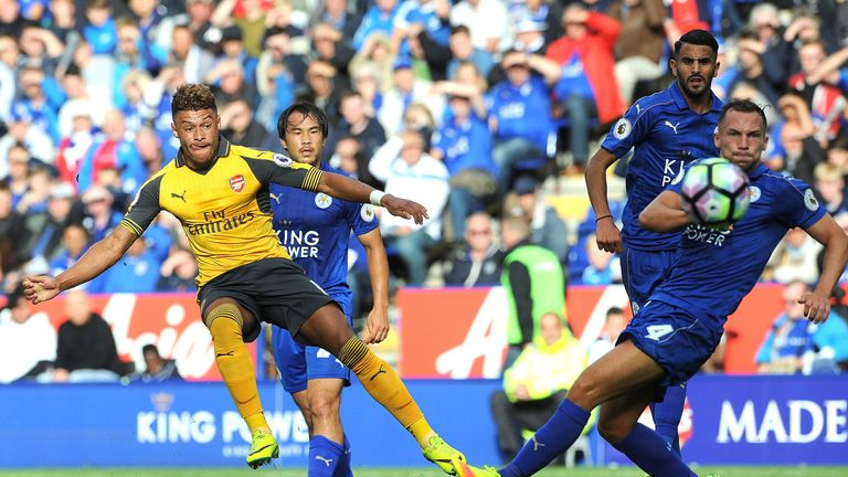 Alex Oxlade-Chamberlain (L) takes a shot at goal under pressure from Danny Drinkwater (R)