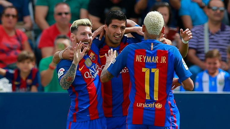 Lionel Messi (L) celebrates scoring their opening goal with teammate Luis Suarez (2nd R) and Neymar