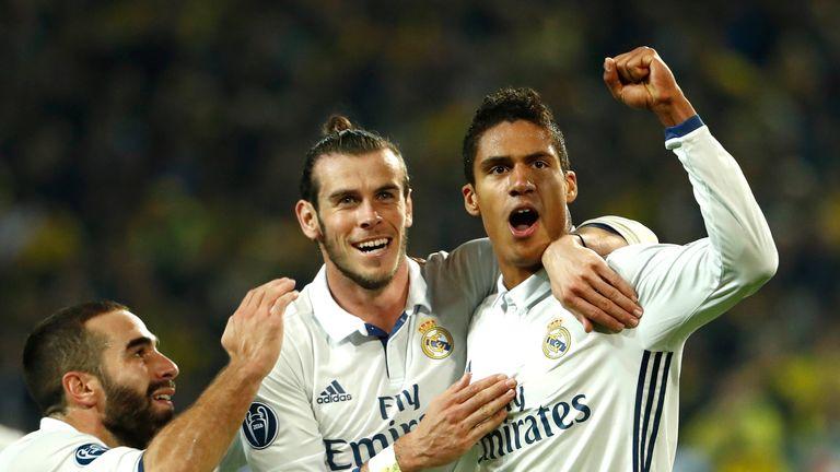 Real defender Raphael Varane (R) celebrates with Gareth Bale after putting Madrid 2-1 ahead at Dortmund