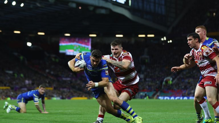 Declan Patton of Warrington scores the opening try despite the challenge from John Bateman of Wigan