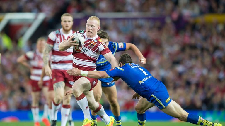 Wigan's Liam Farrell evades the tackle of Warrington's Kurt Gidley