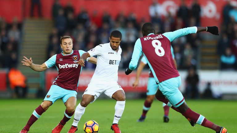 Wayne Routledge (middle) tussles with Mark Noble