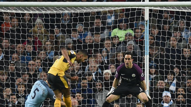 Theo Walcott scores his team's first goal past Manchester City's Chilean goalkeeper Claudio Bravo
