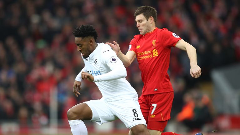 Leroy Fer of Swansea City (L) is put under pressure from James Milner of Liverpool (R)