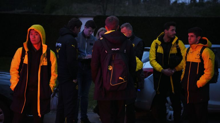 Borussia Dortmund players wait after their team bus was damaged by three explosions