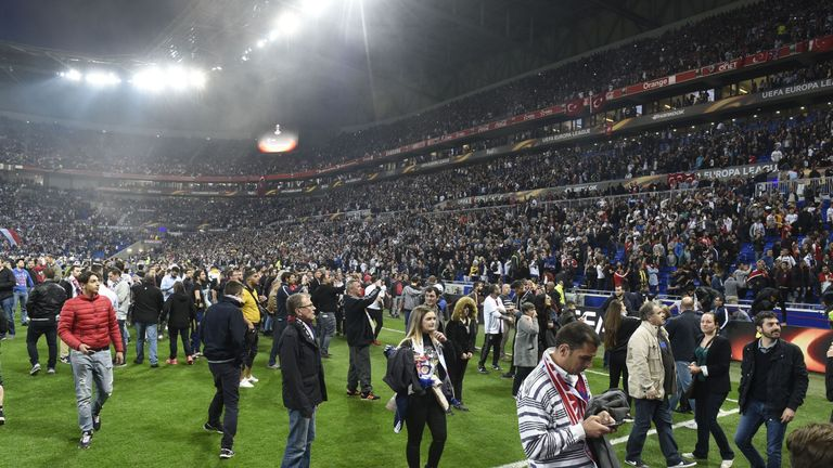 People stand on the field as Besiktas and Lyon fans fight in the tribunes