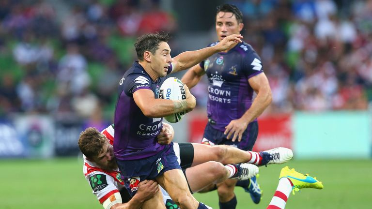 Billy Slater of the Storm is tackled by Gareth Widdop and Will Matthews of the Dragons