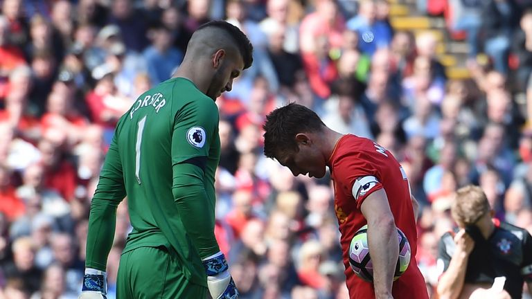 Southampton's Fraser Forster eyes up Liverpool's English midfielder James Milner before the spot-kick is taken
