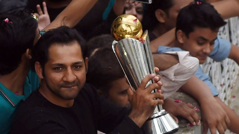 Pakistan skipper Sarfraz Ahmed holds the ICC Champions Trophy aloft to fans in Karachi