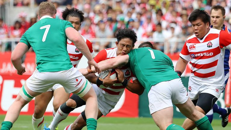 Japan's Yoshitaka Tokunaga is tackled by Ireland's Cian Healy (R) and Dan Leavy (L)