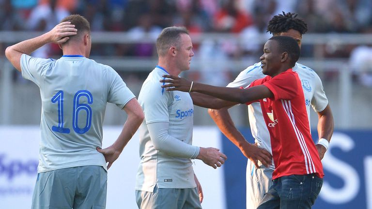 Wayne Rooney is hugged by a Manchester United fan in Tanzania during Everton's friendly