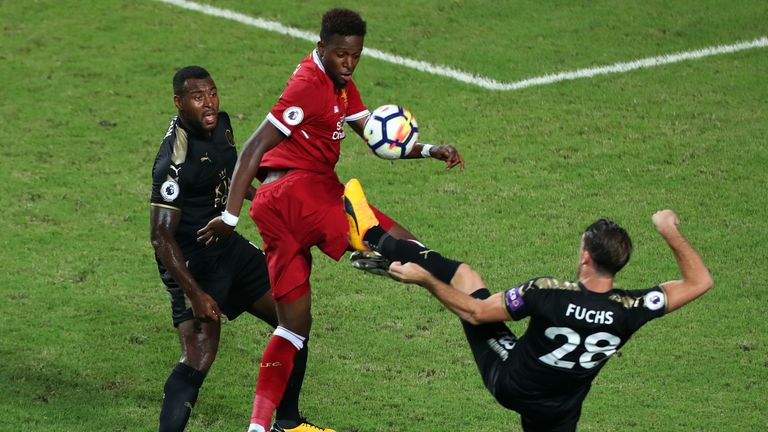 Divock Origi battles for the ball with Wes Morgan and Christian Fuchs in Hong Kong