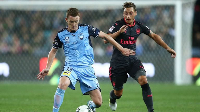 Mesut Ozil challenges Brandon O'Neill during the first half