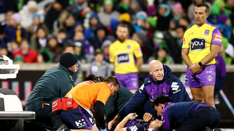 Billy Slater receives treatment after a tackle by Canberra's Sia Soliola