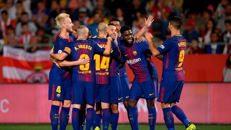 Barcelona players celebrate after taking the lead through a Girona own goal