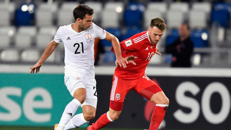Otar Kakabadze and Aaron Ramsey vie for the ball
