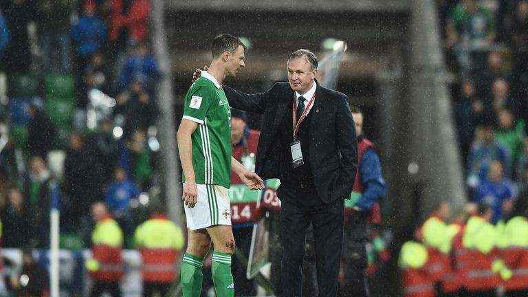 Northern Ireland manager Michael O'Neill consoles Jonny Evans after defeat to Switzerland