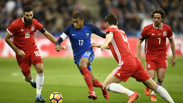 Kylian Mbappe takes on Joe Ledley and Ben Davies at the Stade de France