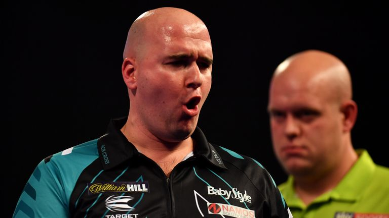 Rob Cross celebrates during his semi-final Match as Michael van Gerwen looks on