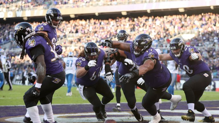 Alex Collins (L) wins the tug-of-war celebration with his Baltimore Ravens team-mates
