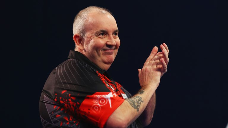 Phil Taylor of England walks onto the stage prior to the second round match against Justin Pipe